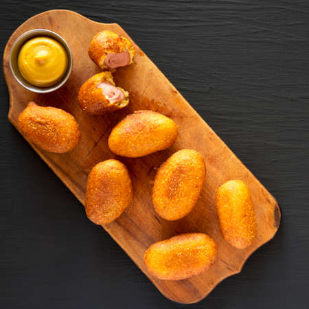 Homemade Mini Corn Dogs on a rustic wooden board on a black background, top view. Flat lay, overhead, from above. Copy space. Stockfoto