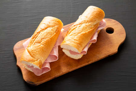 Homemade Parisian Jambon-Beurre Sandwich on a rustic wooden board on a black surface, side view. Stockfoto