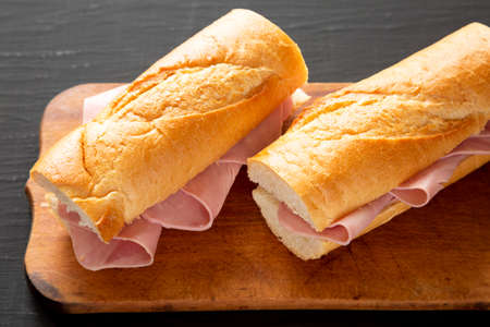Homemade Parisian Jambon-Beurre Sandwich on a rustic wooden board on a black background, side view. Close-up. Stockfoto