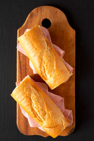 Homemade Parisian Jambon-Beurre Sandwich on a rustic wooden board on a black surface, top view. Flat lay, overhead, from above.
