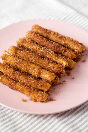 Home-baked Churro Bites on a pink plate on cloth, side view. Close-up. Stockfoto