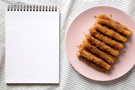 Home-baked Churro Bites on a pink plate, blank notepad, top view. Flat lay, overhead, from above.