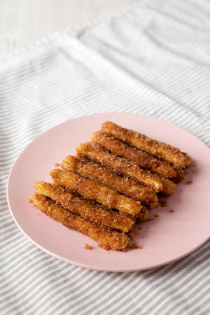 Home-baked Churro Bites on a pink plate on cloth, low angle view. Copy space.