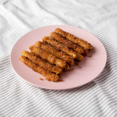Home-baked Churro Bites on a pink plate on cloth, low angle view. Stockfoto