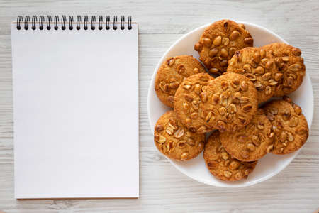 Homemade Cookies with Peanuts on a white plate, blank notepad on a white wooden background, top view. Flat lay, overhead, from above.