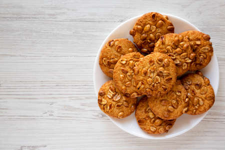 Homemade Cookies with Peanuts on a white plate, top view. Flat lay, overhead, from above. Copy space. Stockfoto