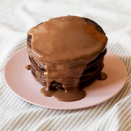 Homemade Chocolate Pancakes on a pink plate, side view. Stockfoto