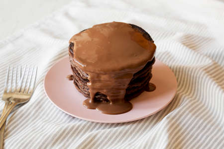Homemade Chocolate Pancakes on a pink plate, low angle view.