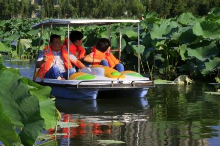 despacio: LUANNAN CITY - JULY 25 barco de placer de conducir lentamente en el agua en un parque el 25 de julio de 2013, la ciudad de Luannan, provincia de Hebei, China