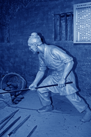 ancient blacksmith: TANGSHAN - OCTOBER 18: The han dynasty iron smelting sculpture in kailuan museum on october 18, 2013, tangshan city, hebei province, China.   Editorial