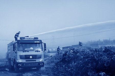 tangshan city: TANGSHAN - NOVEMBER 20: firefighters in sprinkler at the scene of the fire, November 20, 2013, tangshan city, hebei province, China.