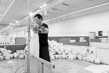 semifinished: LUANNAN COUNTY - DECEMBER 20: The workers were packing cotton reel thread in a production workshop, in the ZeAo spinning LTD., on December 20, 2013, Luannan county, hebei province, China.   Editorial