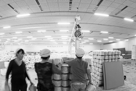 semifinished: LUANNAN COUNTY - DECEMBER 20: The Combed cotton yarn semi-finished products and workers in the ZeAo spinning LTD., on December 20, 2013, Luannan county, hebei province, China.