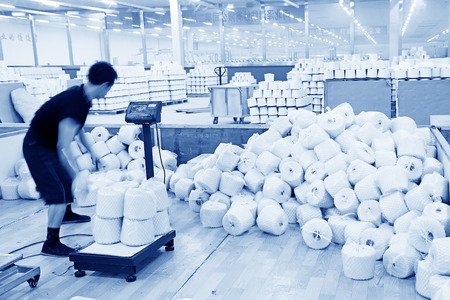 LUANNAN COUNTY - DECEMBER 20: The workers were packing cotton reel thread in a production workshop, in the ZeAo spinning LTD., on December 20, 2013, Luannan county, hebei province, China.