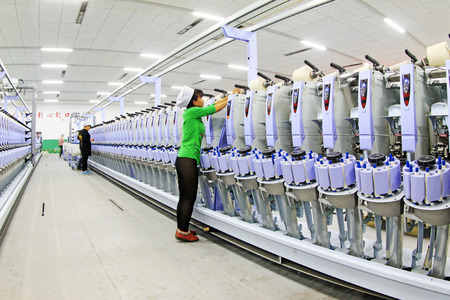 LUANNAN COUNTY - DECEMBER 20: The spinning machinery and equipment in a production workshop, in the ZeAo spinning LTD., on December 20, 2013, Luannan county, hebei province, China.