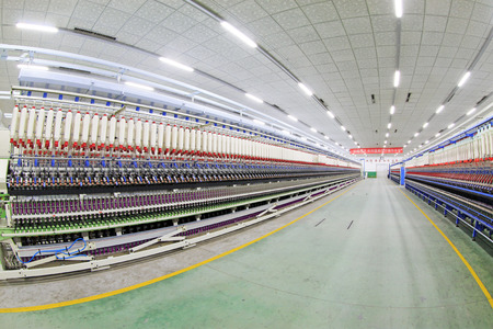 spindles: LUANNAN COUNTY - DECEMBER 20: The spinning machinery and spindles in a production workshop, in the ZeAo spinning LTD., on December 20, 2013, Luannan county, hebei province, China.