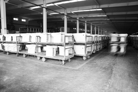 LUANNAN COUNTY - JANUARY 5: The worker and ceramic closestool products assemblies in a warehouse, in the ZhongTong Ceramics Co., Ltd. January 5, 2014, Luannan county, Hebei Province, China.  Editorial