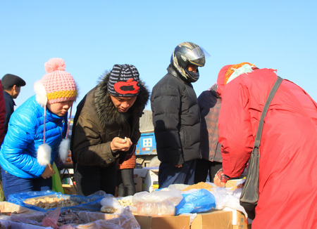 inquiries: LUANNAN COUNTY - JANUARY 28: The customer and vendor in bargaining, before a seafood stalls, on january 28, 2014, Luannan county, Hebei province, China.