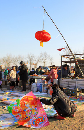 bargaining: LUANNAN COUNTY - JANUARY 28: The customer and vendor in bargaining, before a New Year pictures stalls, on january 28, 2014, Luannan county, Hebei province, China.