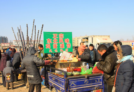LUANNAN COUNTY - JANUARY 28: The customer and vendor in bargaining, before a pancakes stalls, on january 28, 2014, Luannan county, Hebei province, China.