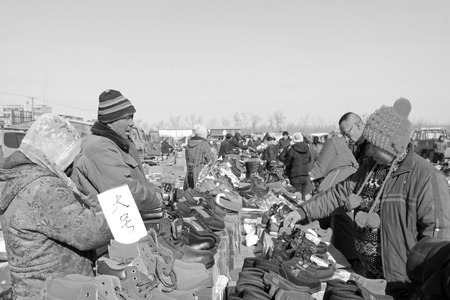 inquiries: LUANNAN COUNTY - JANUARY 28: The customer and vendor in bargaining, before a footwear stalls, on january 28, 2014, Luannan county, Hebei province, China.  Editorial