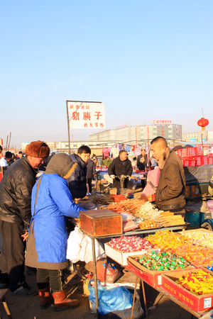 LUANNAN COUNTY - JANUARY 28: The customer and vendor in bargaining, before a cooked food stalls, on january 28, 2014, Luannan county, Hebei province, China.