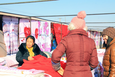 color consultation: LUANNAN COUNTY - JANUARY 28: The customer and vendor in bargaining, before a cloth stalls, on january 28, 2014, Luannan county, Hebei province, China.