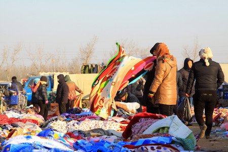 LUANNAN COUNTY - JANUARY 28: The customer and vendor in bargaining, before a cloth stalls, on january 28, 2014, Luannan county, Hebei province, China.