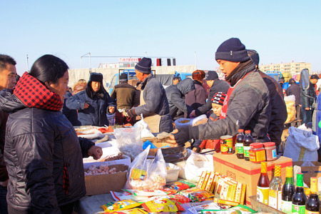 bargaining: LUANNAN COUNTY - JANUARY 28: The customer and vendor in bargaining, before a seasoning stalls, on january 28, 2014, Luannan county, Hebei province, China.