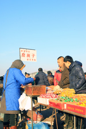 bargaining: LUANNAN COUNTY - JANUARY 28: The customer and vendor in bargaining, before a cooked food stalls, on january 28, 2014, Luannan county, Hebei province, China.