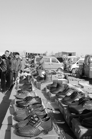 LUANNAN COUNTY - JANUARY 28: The customer and vendor in bargaining, before a footwear stalls, on january 28, 2014, Luannan county, Hebei province, China.  Editorial