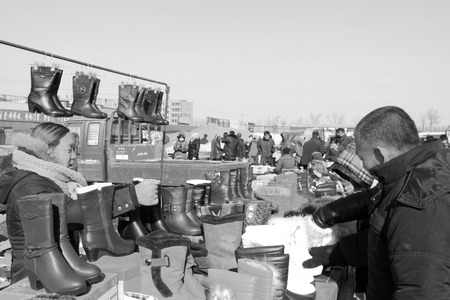 bargaining: LUANNAN COUNTY - JANUARY 28: The customer and vendor in bargaining, before a footwear stalls, on january 28, 2014, Luannan county, Hebei province, China.  Editorial