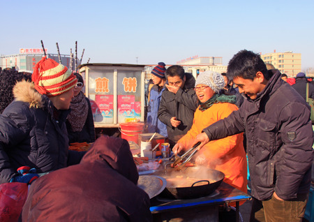 bargaining: LUANNAN COUNTY - JANUARY 28: The customer and vendor in bargaining, before a pancakes cooked food stalls, on january 28, 2014, Luannan county, Hebei province, China.