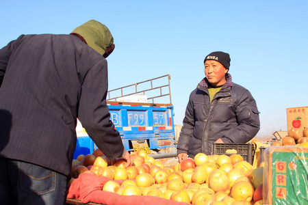 bargaining: LUANNAN COUNTY - JANUARY 28: The customer and vendor in bargaining, before a fruit stalls, on january 28, 2014, Luannan county, Hebei province, China.