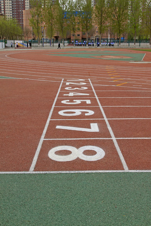 green number on plastic runway in a sports ground in a middle\ school