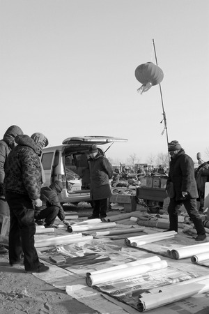 inquiries: LUANNAN COUNTY - JANUARY 28: The customer and vendor in bargaining, before a New Year pictures stalls, on january 28, 2014, Luannan county, Hebei province, China.
