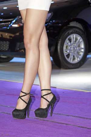 Beauty model dressed in high heels in purple background, closeup of photo photo