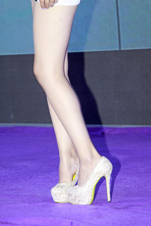 Beauty model dressed in white ornamental engraving high-heeled shoes on purple carpet   photo