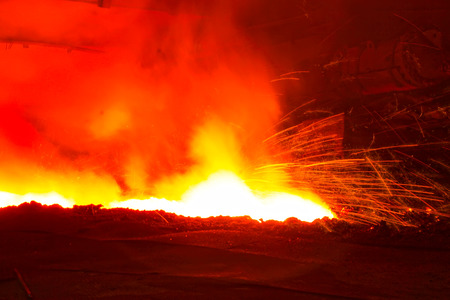 spewing: iron works blast furnace taphole spewing molten iron, closeup of photo