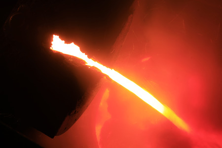 iron works: flowing molten iron in the iron works blast furnace taphole, closeup of photo Stock Photo