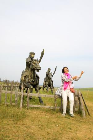 mongolia horse: WULANBUTONG GRASSLAND - JULY 18: A woman standing next to the Mongolian cavalry sculpture in the WuLanBuTong grassland on July 18, 2014, Inner Mongolia autonomous region, China.