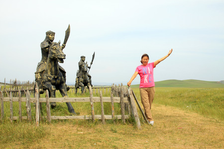 WULANBUTONG GRASSLAND - JULY 18: A woman standing next to the Mongolian cavalry sculpture in the WuLanBuTong grassland on July 18, 2014, Inner Mongolia autonomous region, China.