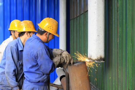 conduit: TANGSHAN - JUNE 19: workers welding metallic conduit in a factory, on June 19, 2014, Tangshan city, Hebei Province, China