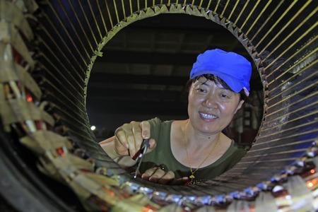 tangshan city: TANGSHAN - JUNE 20: Women workers repairing electrical machine in a factory, on June 20, 2014, Tangshan city, Hebei Province, China  Editorial