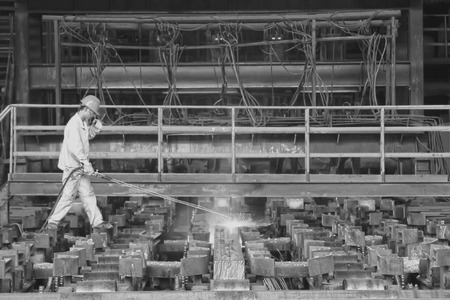 TANGSHAN - JUNE 20: Workers cutting steel ingot behind the continuous casting machine in steel plant, on June 20, 2014, Tangshan city, Hebei Province, China