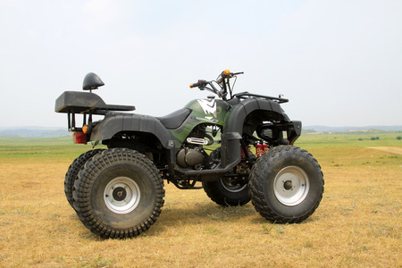 草原では、クローズ アップの写真の 4 つの車輪のオートバイ