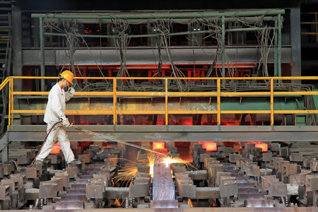 tangshan city: TANGSHAN - JUNE 20: Workers cutting steel ingot behind the continuous casting machine in steel plant, on June 20, 2014, Tangshan city, Hebei Province, China  Editorial