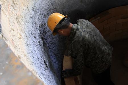 crisol: TANGSHAN - 20 de junio: Los trabajadores se ensamblan acero de crisol interior con ladrillo refractario en una planta de acero, el 20 de junio de 2014, la ciudad de Tangshan, provincia de Hebei, China Editorial