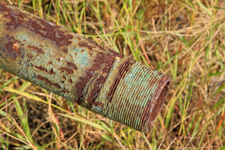Oxidation of rusty metal pipe in the bushes, closeup of photo