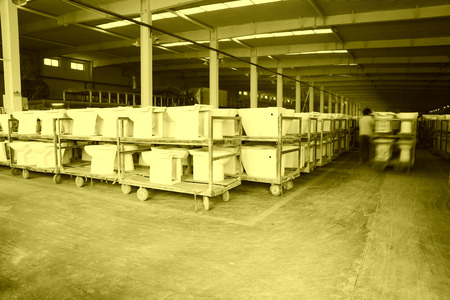 LUANNAN COUNTY - JANUARY 5: The worker and ceramic closestool products assemblies in a warehouse, in the ZhongTong Ceramics Co., Ltd. January 5, 2014, Luannan county, Hebei Province, China.